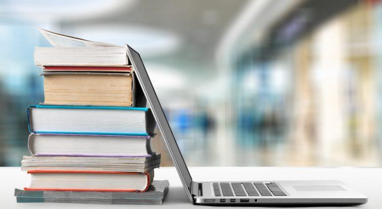 Notebook aberto apoiado em livros