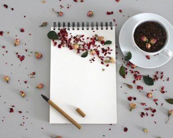 caderneta-sobre-mesa-com-xicara-de-cafe-lapis-epetalas-de-rosas-espalhadas