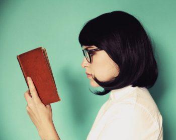mulher-de-cabelo-curto-virada-para-lado-esquerdo-olhando-para-livro-em-suas-maos