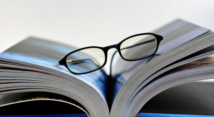 livro aberto com óculos em cima