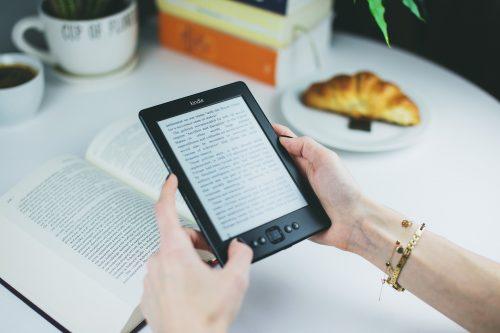 livro na mesa e kindle na mão