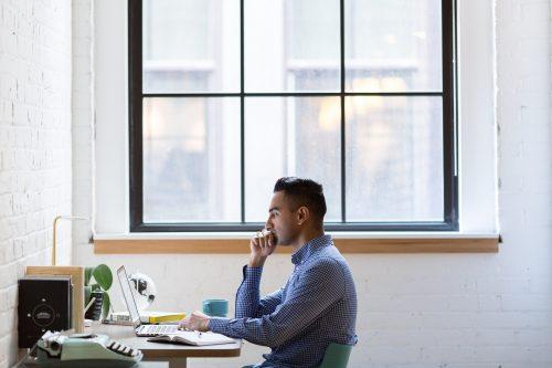 homem sentado mexendo no laptop