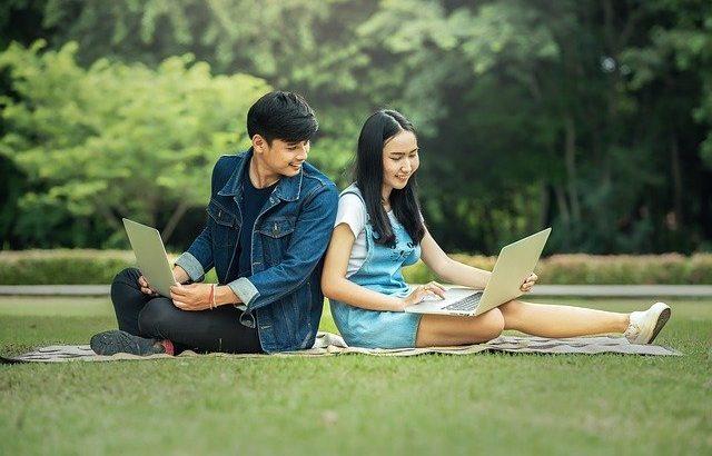 jovens-adultos-sentados-rindo-com-computador