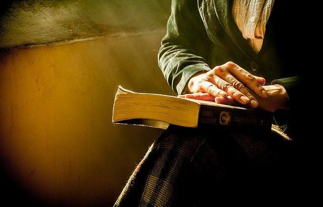 mãos-segurando-livro-fechado-sobre-o-colo