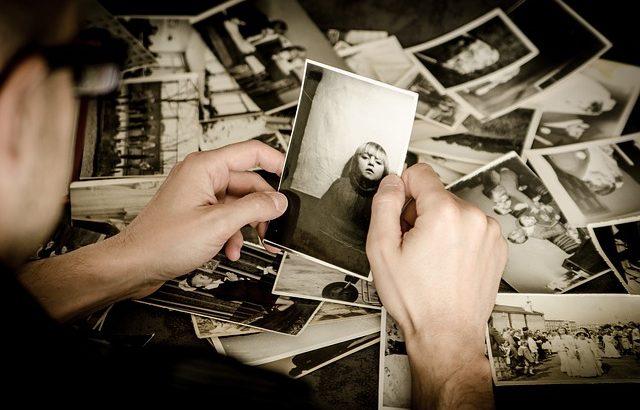 Mão madura segurando foto de criança. O filtro tem tom envelhecido.
