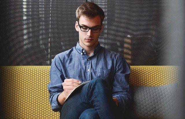 homem-branco-de-oculos-escrevendo-em-caderno