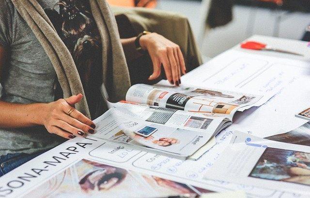 mãos-de-mulher-folheando-uma-revista-em-cima-da-mesa