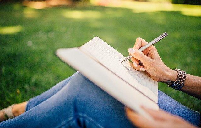 mão-de-mulher-escrevendo-em-caderno-apoiado-no-joelho