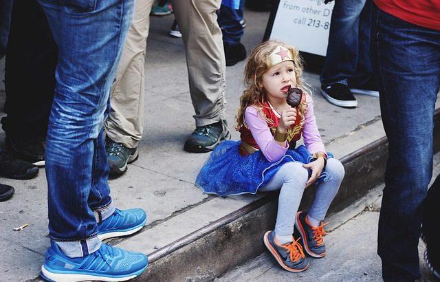 menina-loira-vestida-de-mulher-maravilha-segurando-picole-de-chocolate-sentada-no-meio-fio-com-pessoas-em-volta-e-com-expressao-de-choro